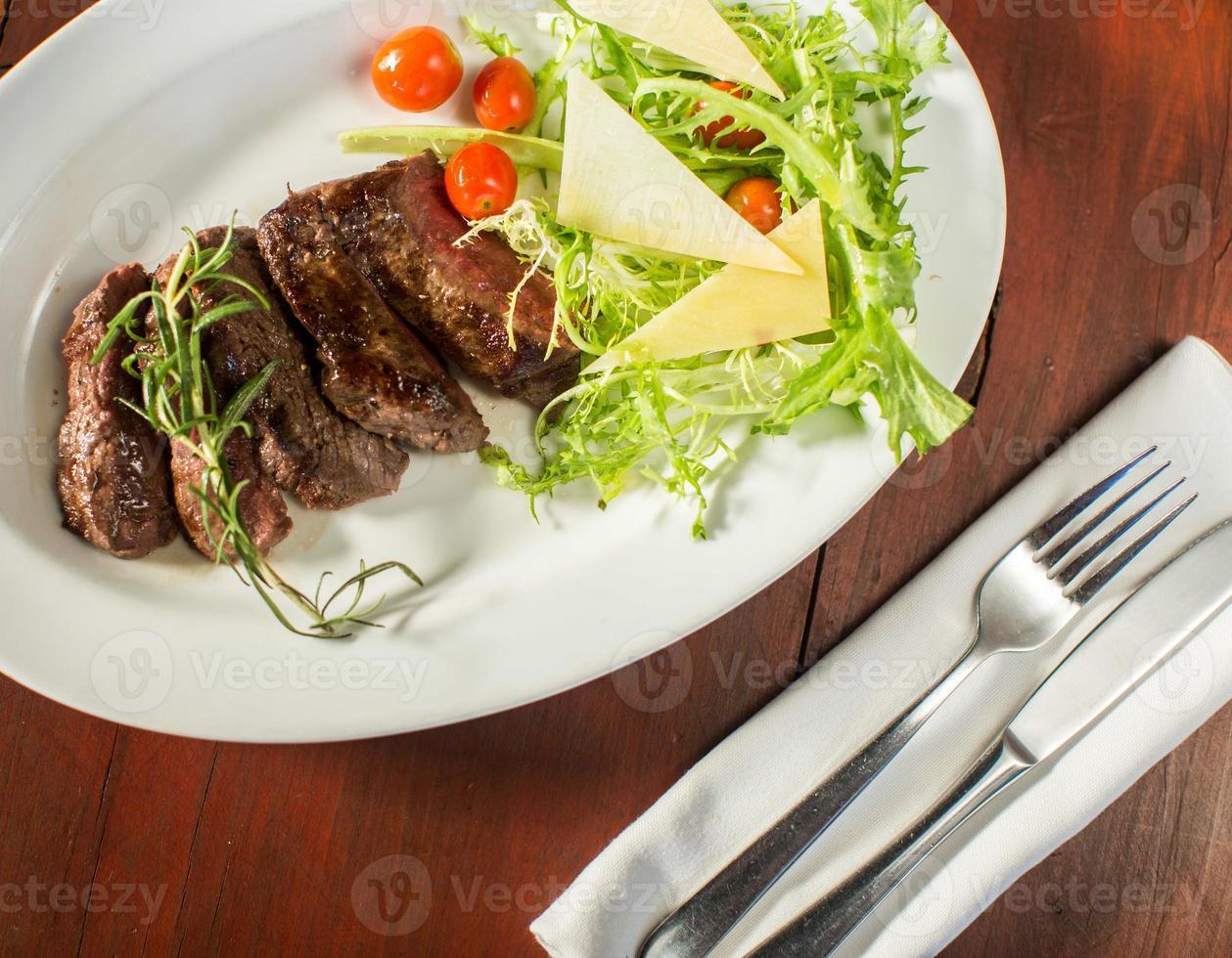 bife com queijo e legumes em um restaurante foto