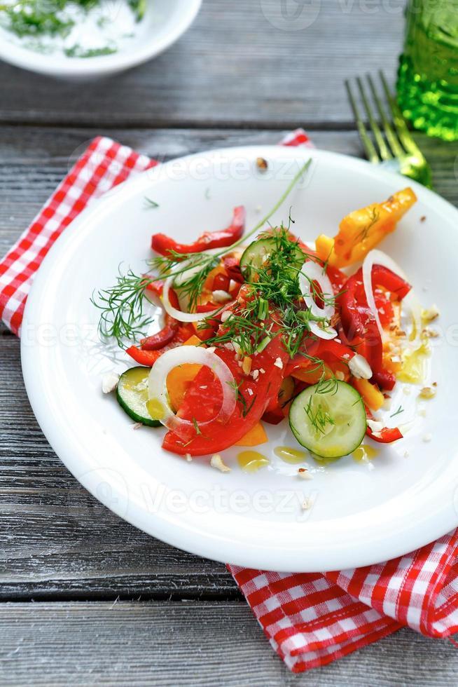 salada de verão com pimentos e rodelas de cebola em chapa branca foto
