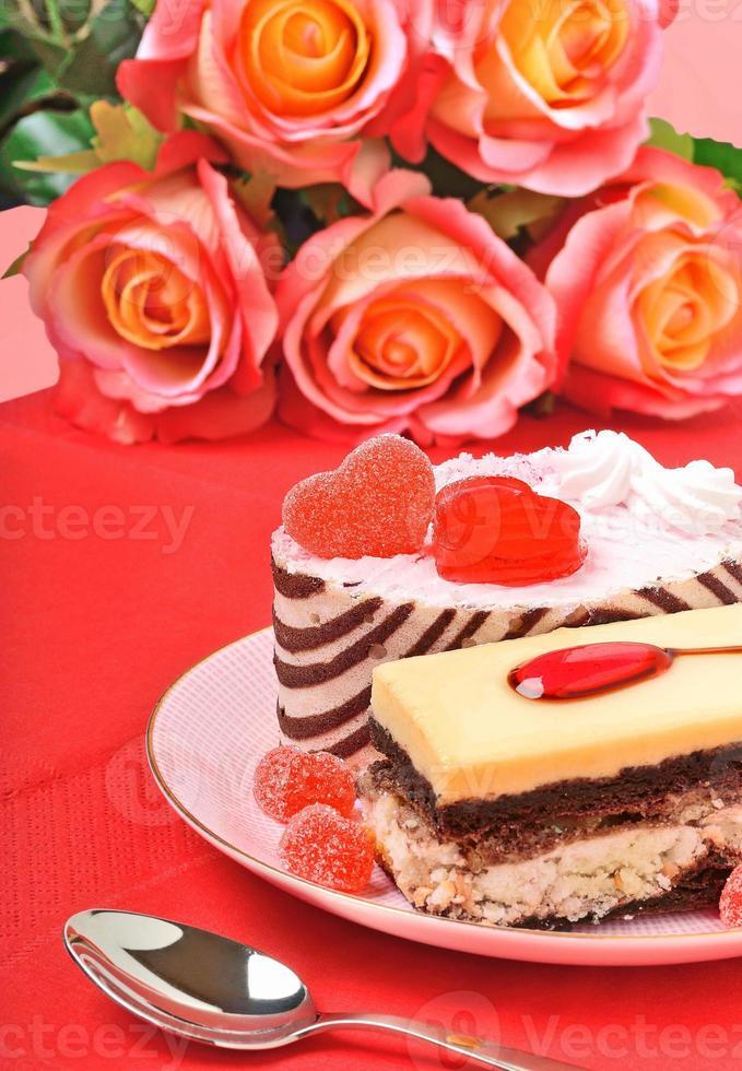 bolos de dia dos namorados, tortas e rosas vermelhas na toalha de mesa vermelha foto