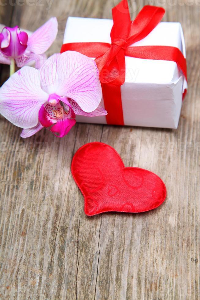 presente de feriado, orquídea e coração vermelho foto