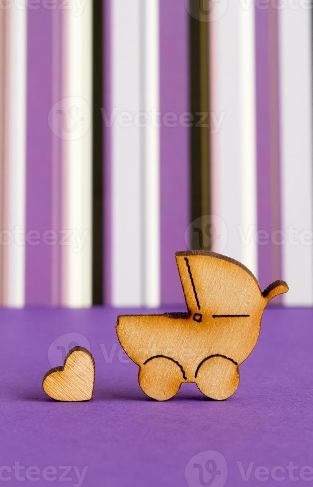 ícone de madeira de carrinho de bebê e coraçãozinho foto