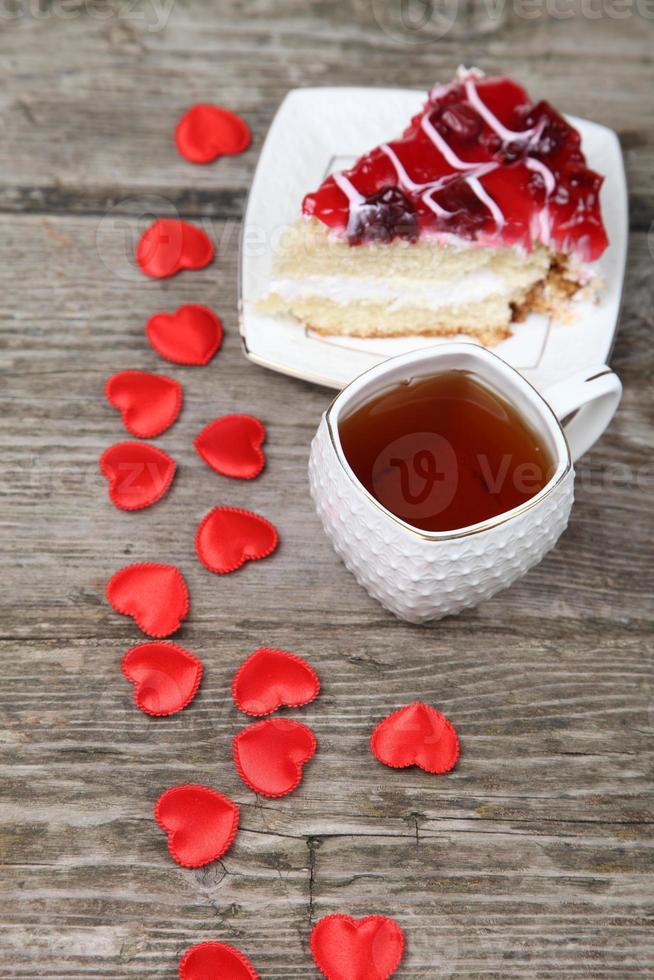 xícara de chá, pedaço de bolo e coração vermelho foto