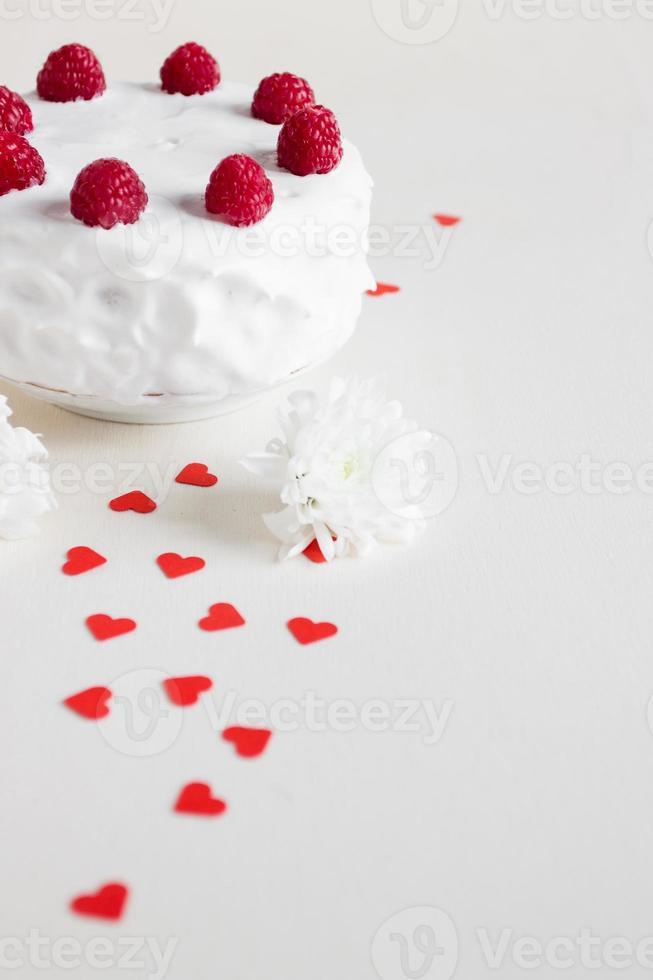 bolo branco com framboesas e corações vermelhos foto