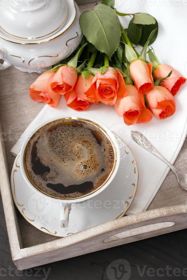 xícara de café e um buquê de rosas foto