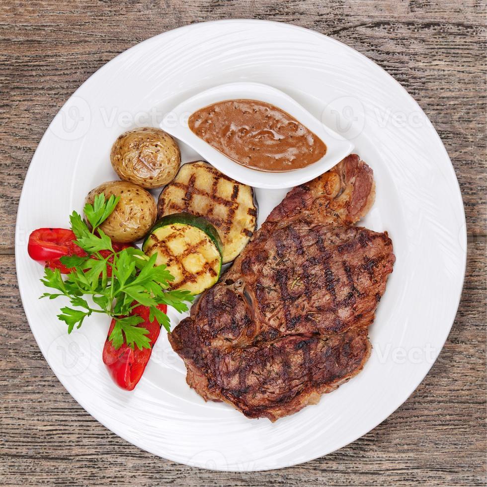 bifes grelhados, batatas assadas e legumes no prato branco foto