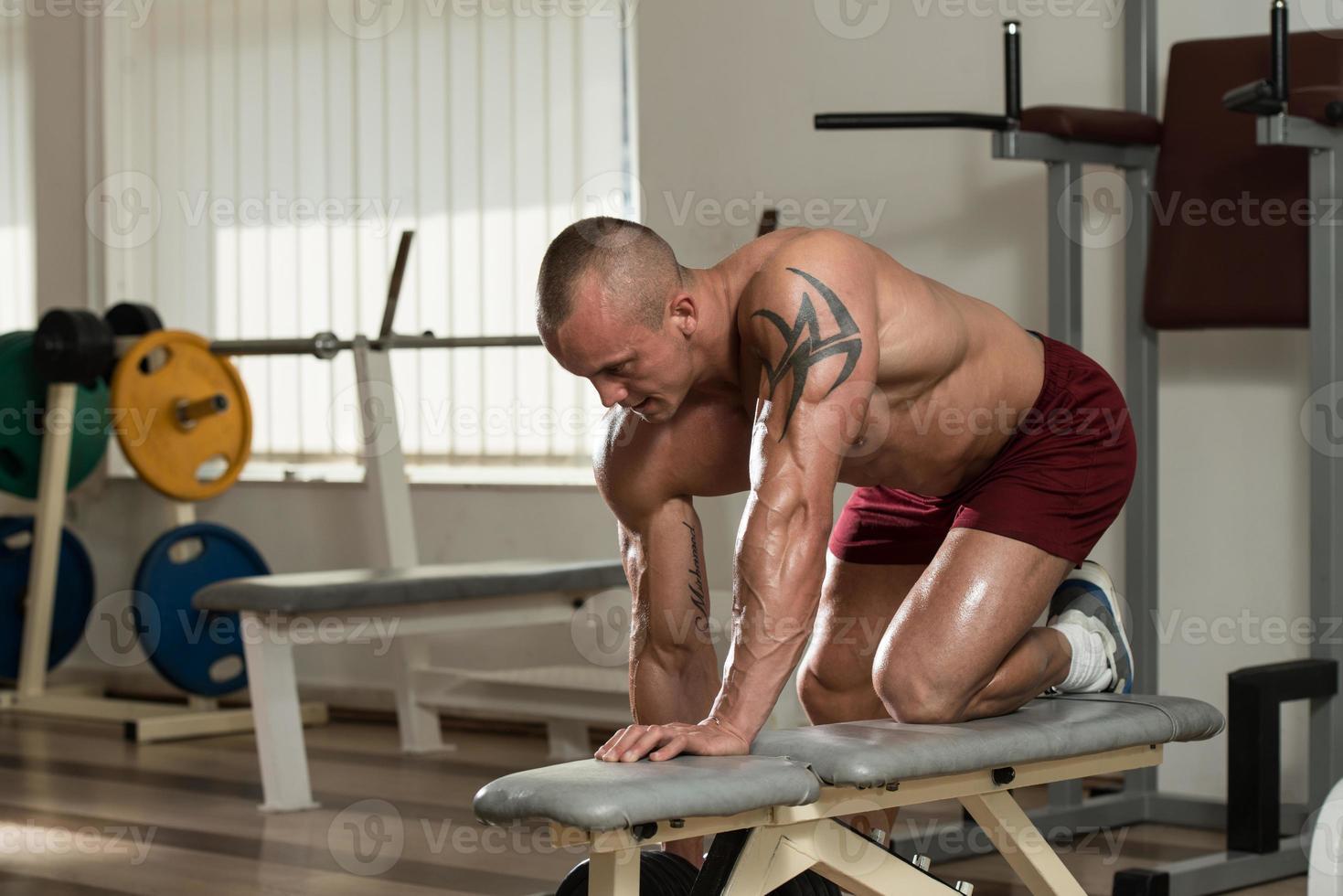 homem saudável, fazendo exercícios traseiros com haltere foto