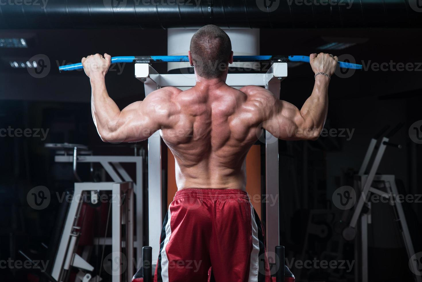 jovem fisiculturista fazendo exercício de peso pesado para as costas foto