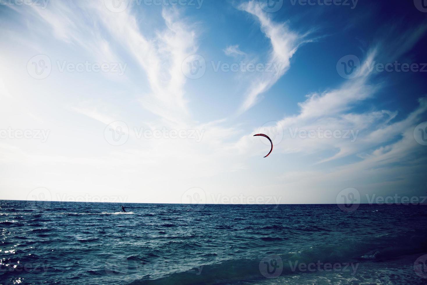 pessoas que gostam de kitesurf na água tropical azul clara foto