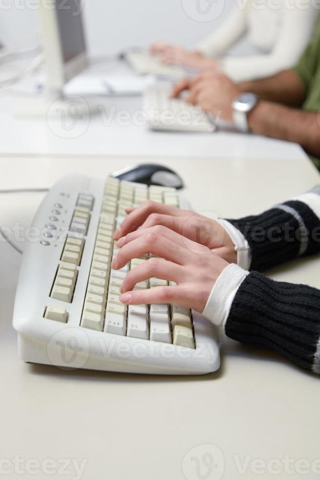 alunos digitando no teclado na aula de informática foto
