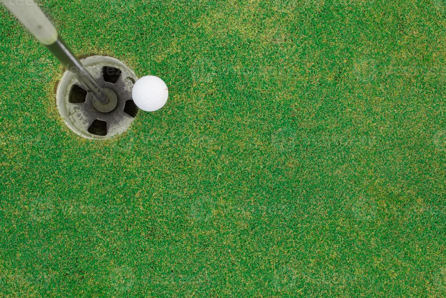 bola de golfe perto do buraco foto