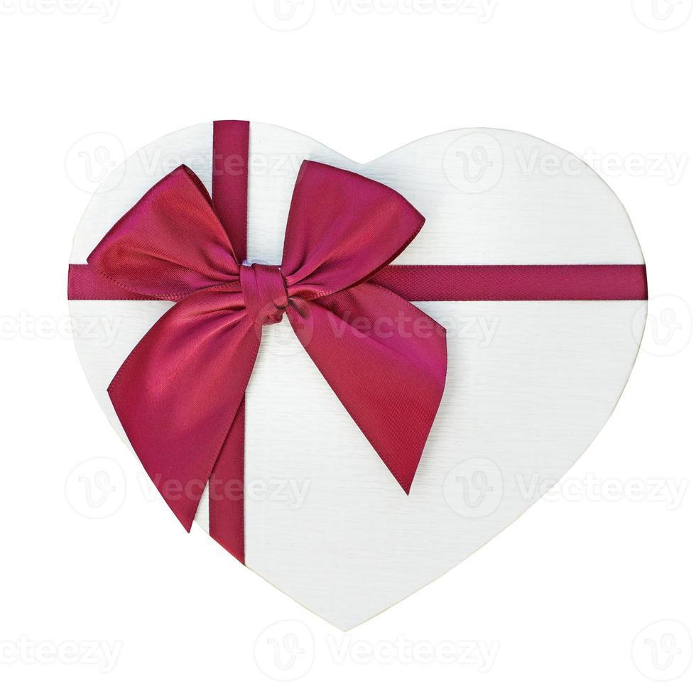 caixa de presente com fita vermelha e laço isolado no branco foto