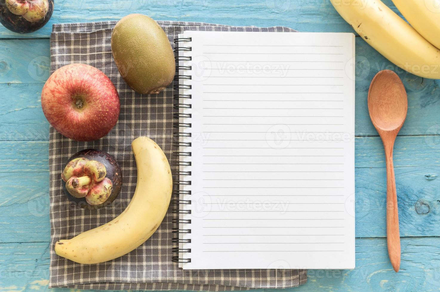 livro de receitas com frutas em fundo de madeira foto