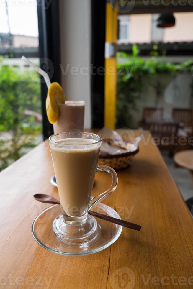 xícara de cappuccino quente com smoothie de banana com chocolate e pão foto