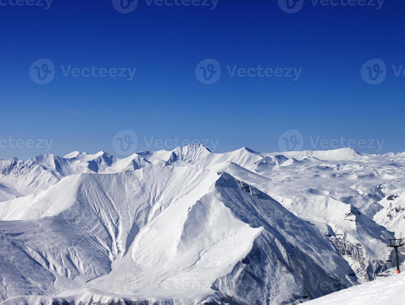 montanhas de inverno e céu azul claro em bom dia foto