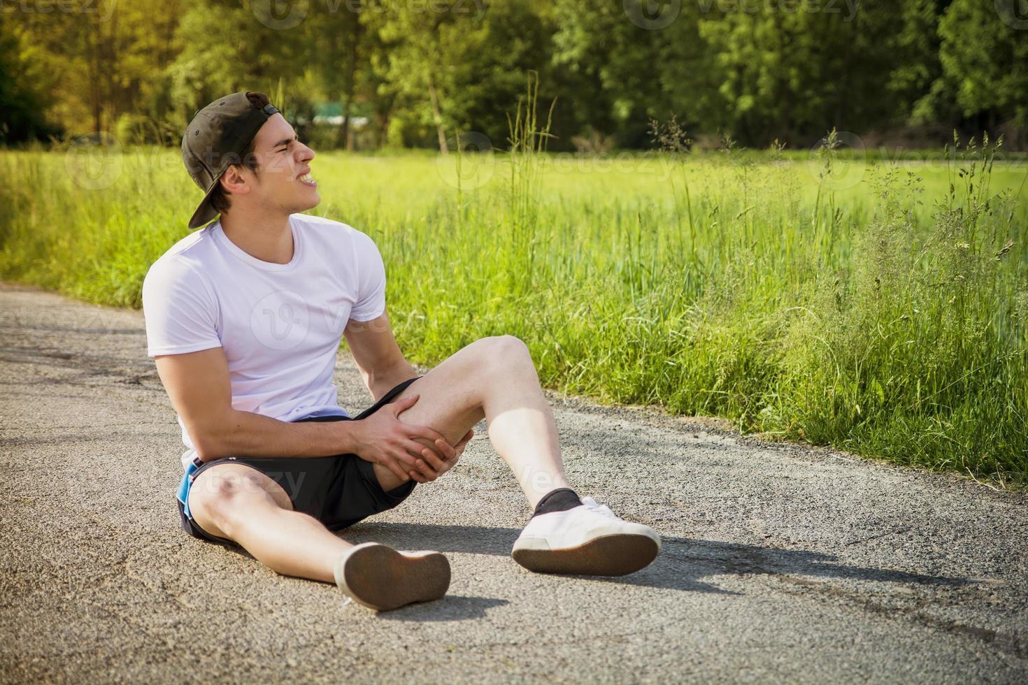 jovem bonito ferido enquanto correndo e correndo na estrada foto