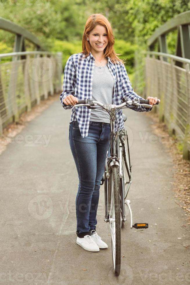 ruiva bonita com sua bicicleta sorrindo para a câmera foto