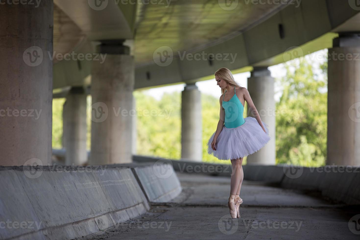 bailarina graciosa fazendo exercícios de dança em uma ponte de concreto foto