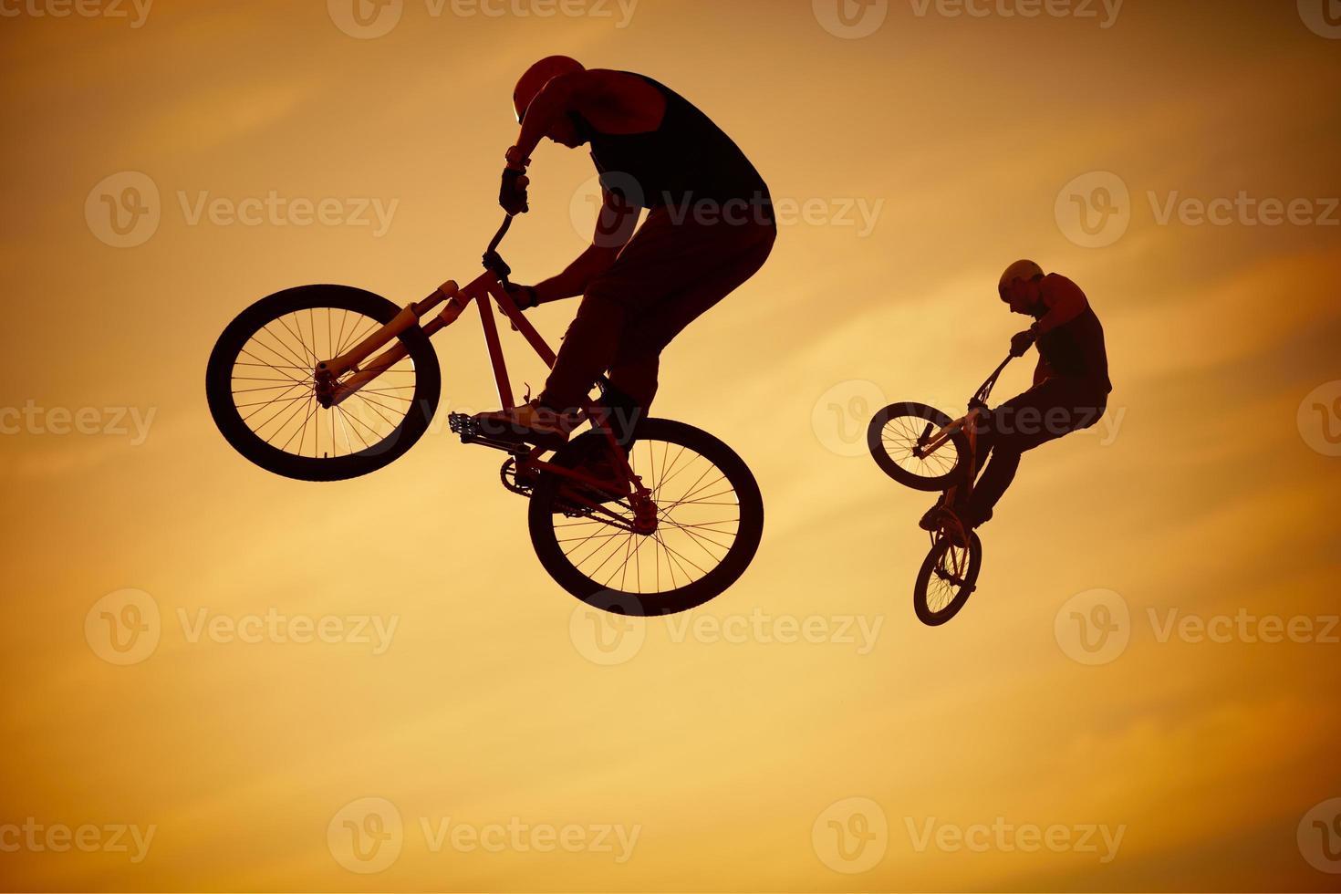 dois homens realizando truques de bmx em suas bicicletas no ar foto