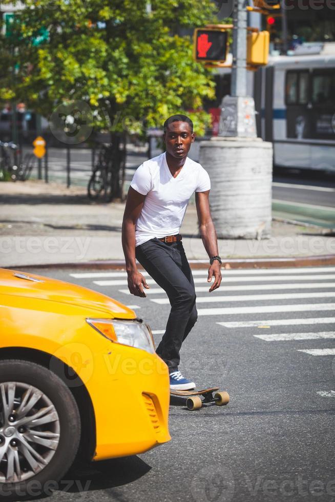 menino negro patinando com longboard na estrada foto
