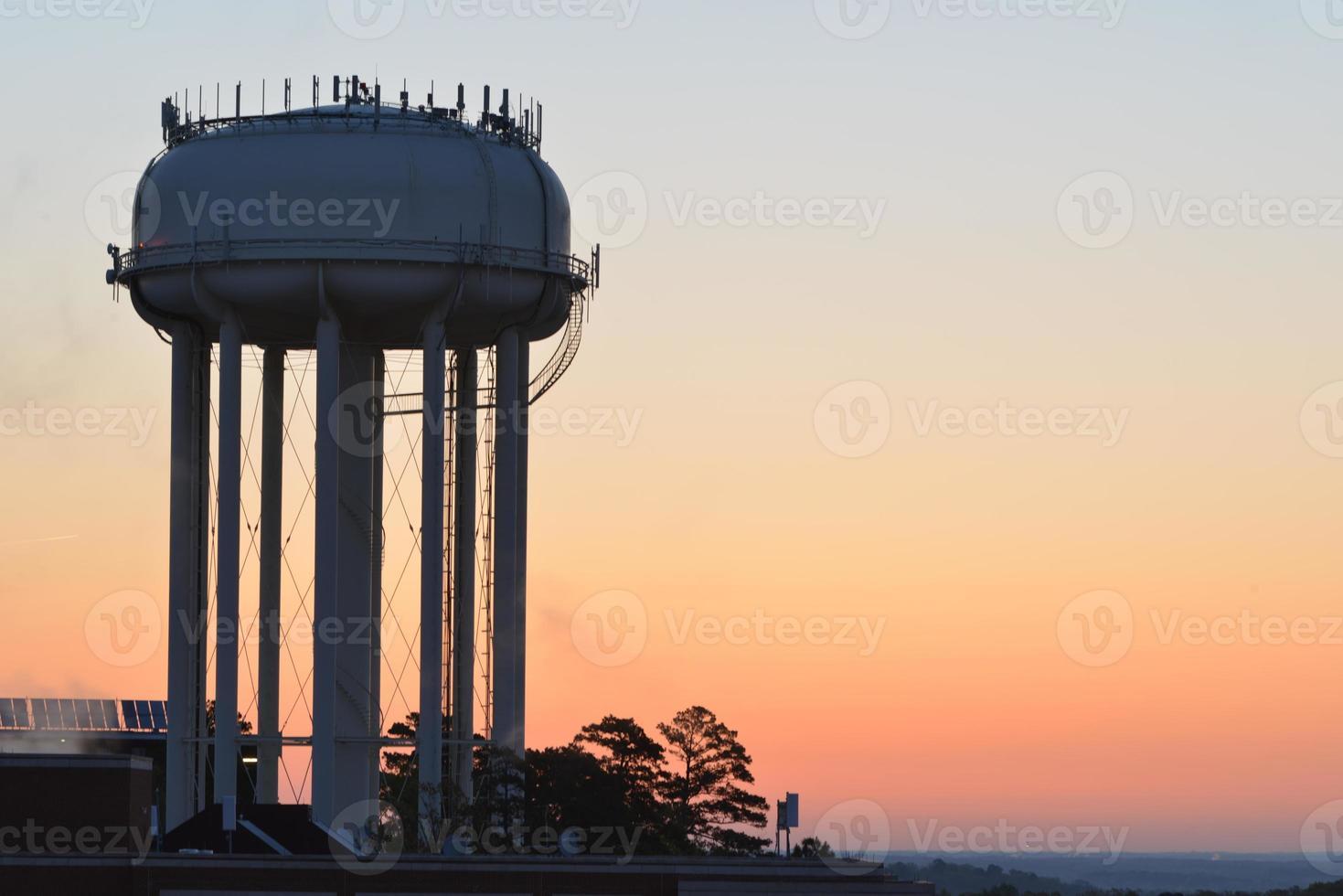 silhueta de torre de água ao nascer do sol foto