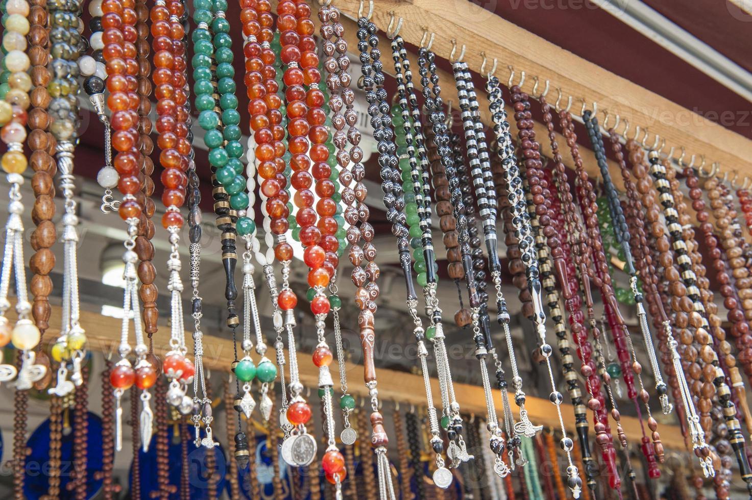 jóias ornamentadas penduradas na banca de mercado foto