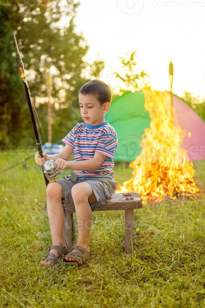 criança em viagem de acampamento aprendendo como; use vara de pescar foto