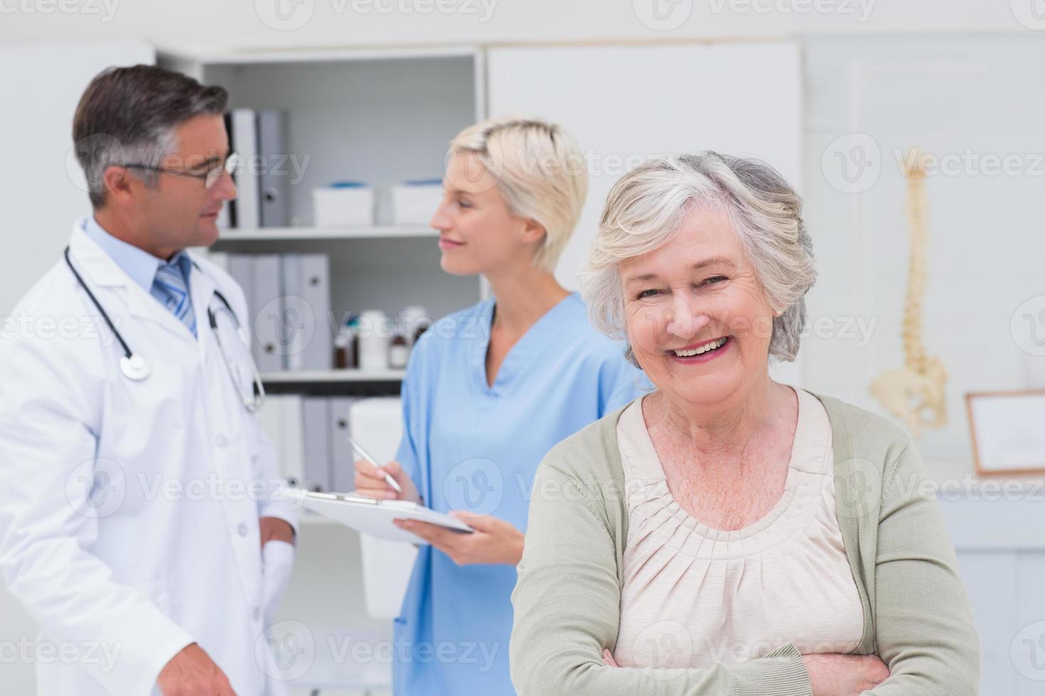 paciente sorrindo enquanto médico e enfermeira discutindo em segundo plano foto