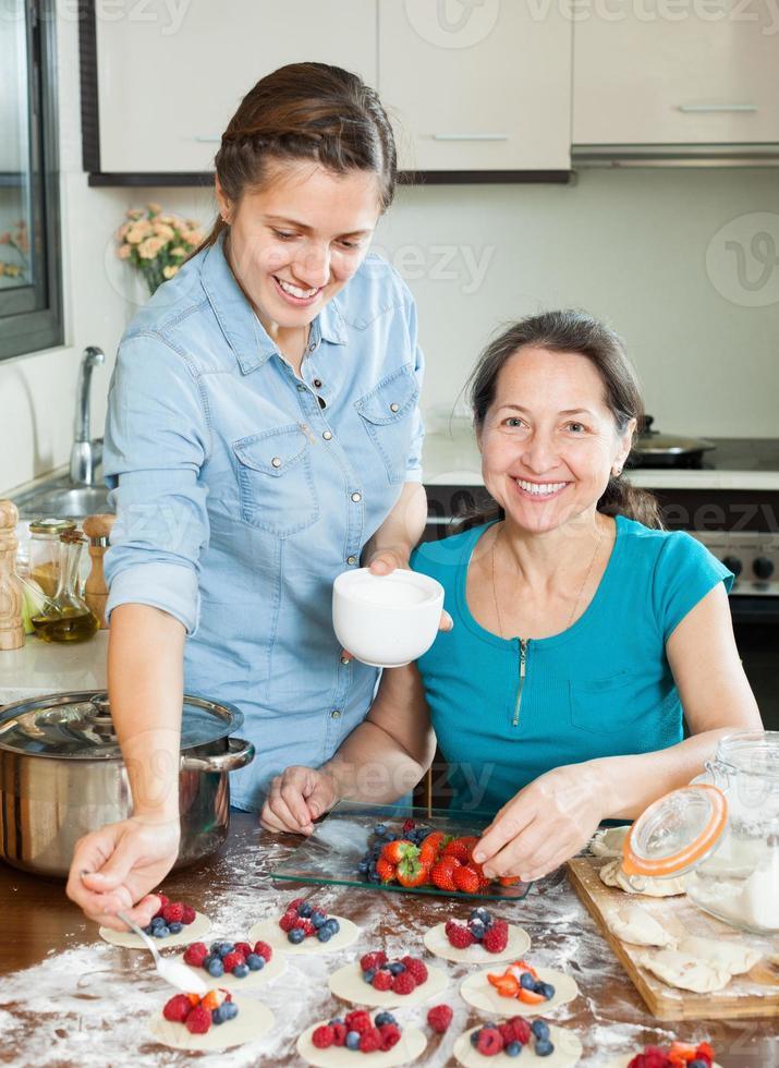 família cozinhar bagas bolinhos juntos foto