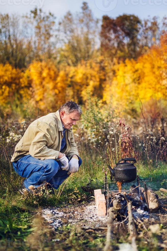 homem ferve chaleira fuligem no fogo foto
