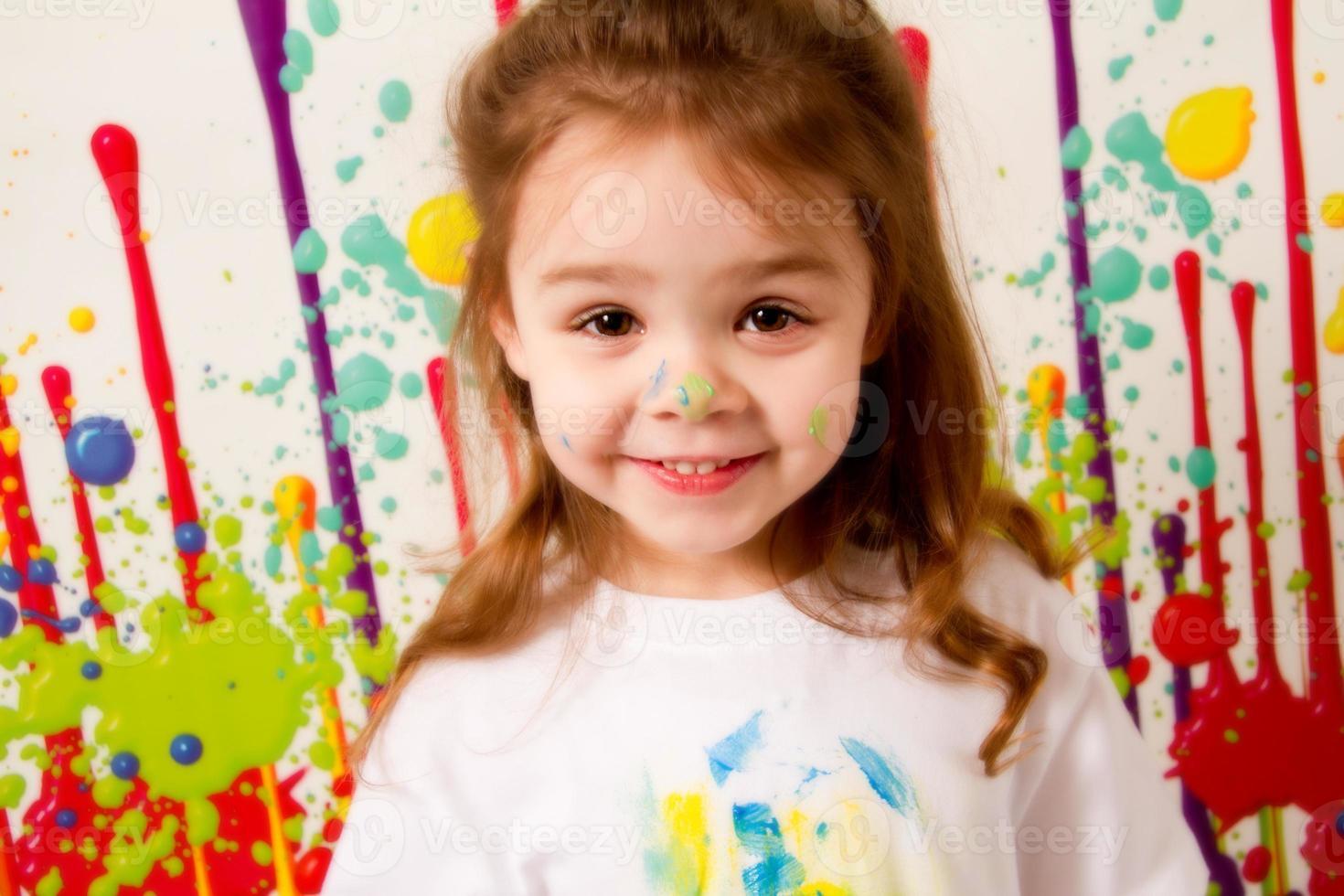 criança feliz, coberta de salpicos de tinta foto