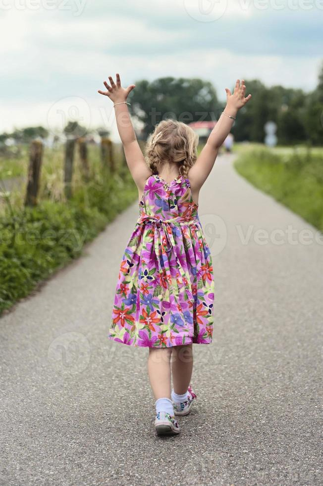 criança andando com as mãos no ar foto