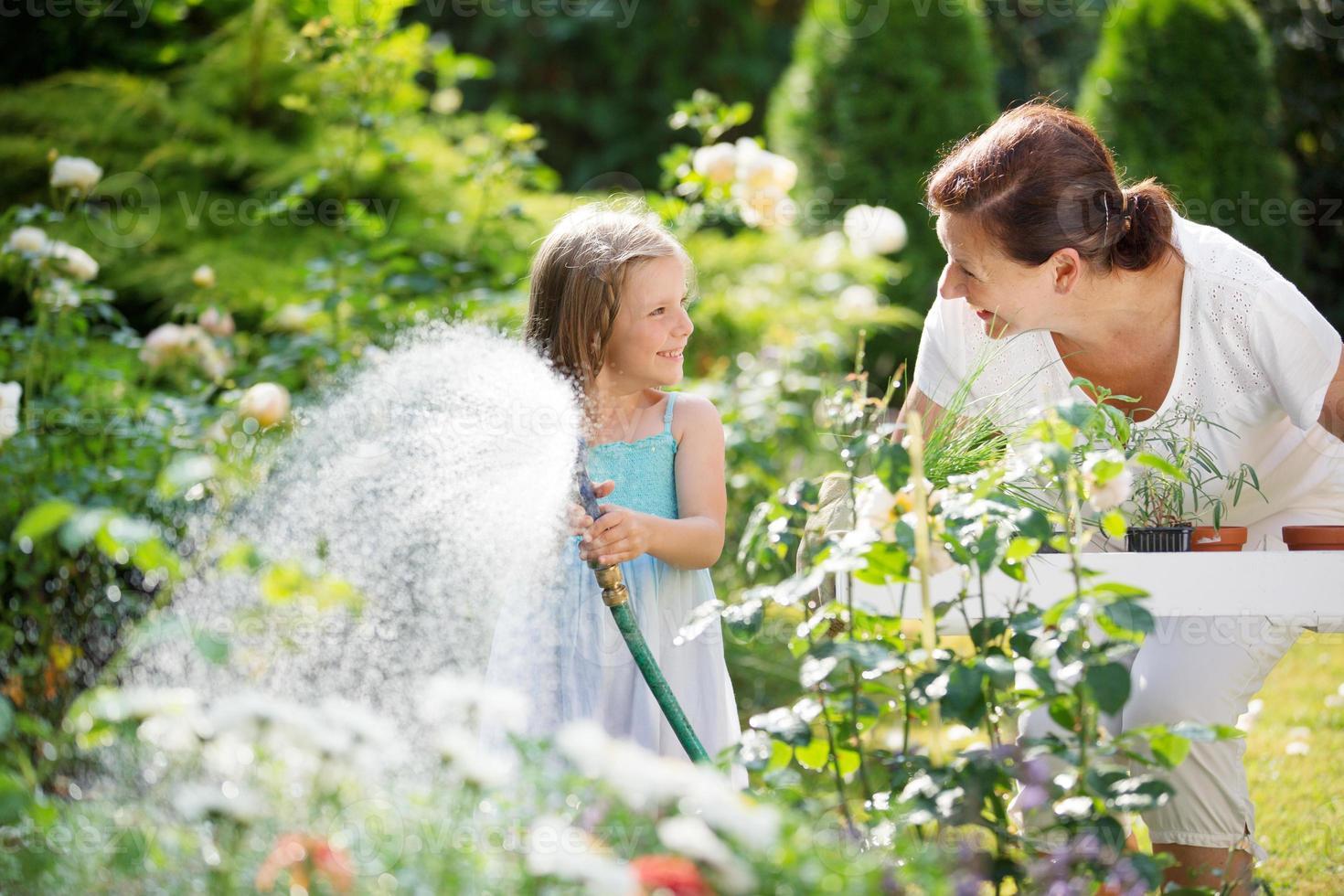 menina e vovó regando flores no jardim foto