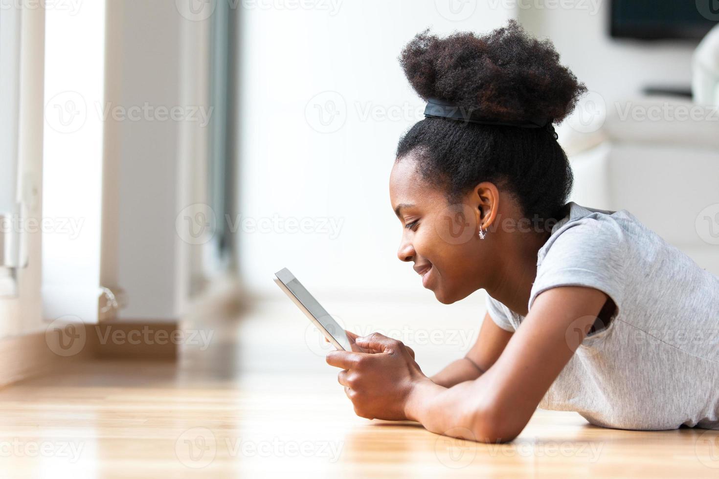 mulher afro-americana usando um tablet tátil foto
