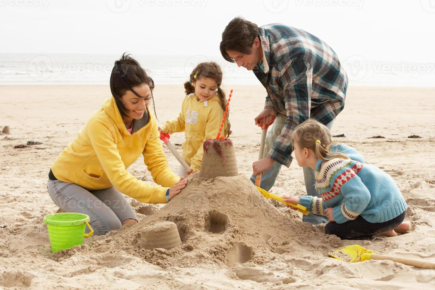 castelo de areia de construção familiar na praia de inverno foto