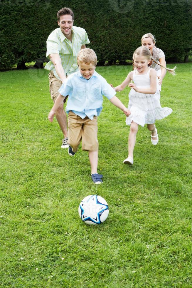 família jogando futebol no jardim foto
