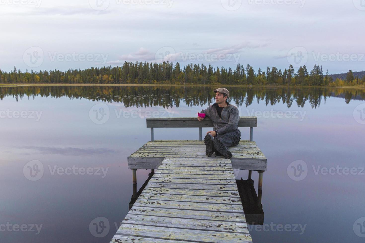 homem sentado no palco no lago foto