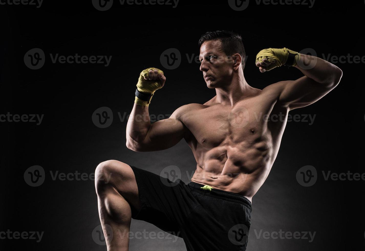 homem musculoso em estúdio em fundo escuro foto
