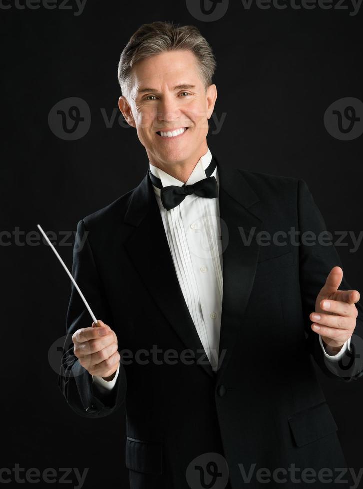 retrato do condutor de música masculino confiante segurando seu bastão foto