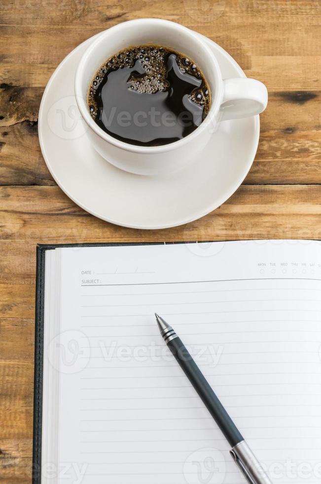 notebook com caneta e xícara de café sobre fundo de madeira. foto