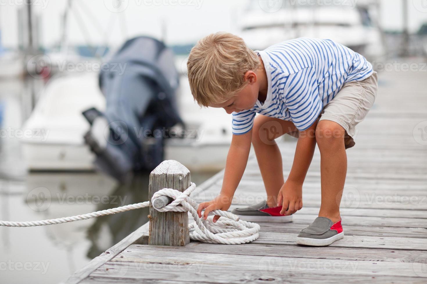 jovem rapaz amarra nó na doca do barco foto