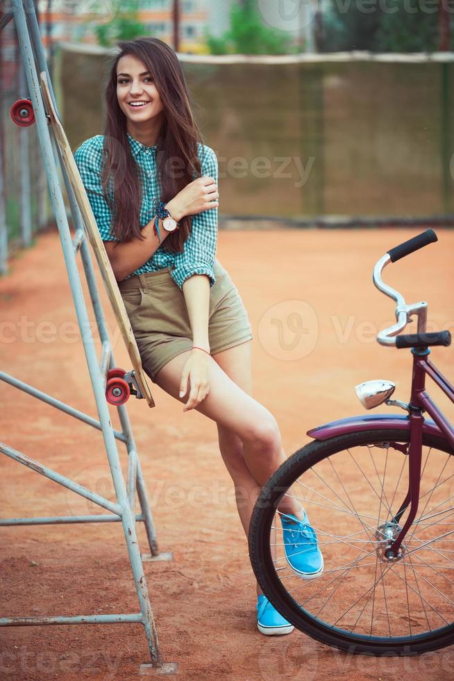 linda garota com longboard e bicicleta foto