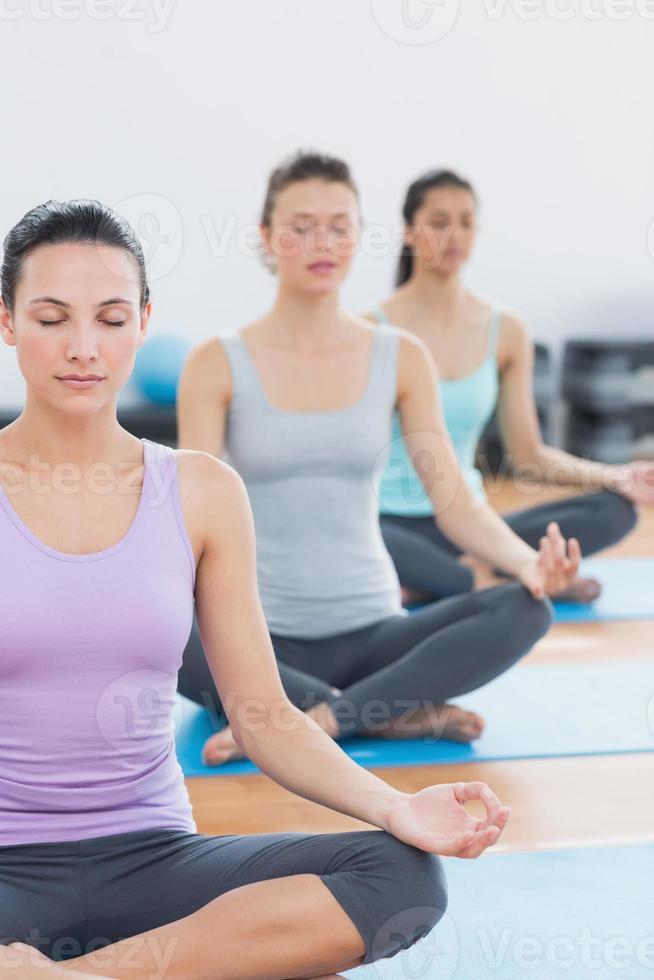 mulheres em postura de lótus, com os olhos fechados no estúdio de fitness foto