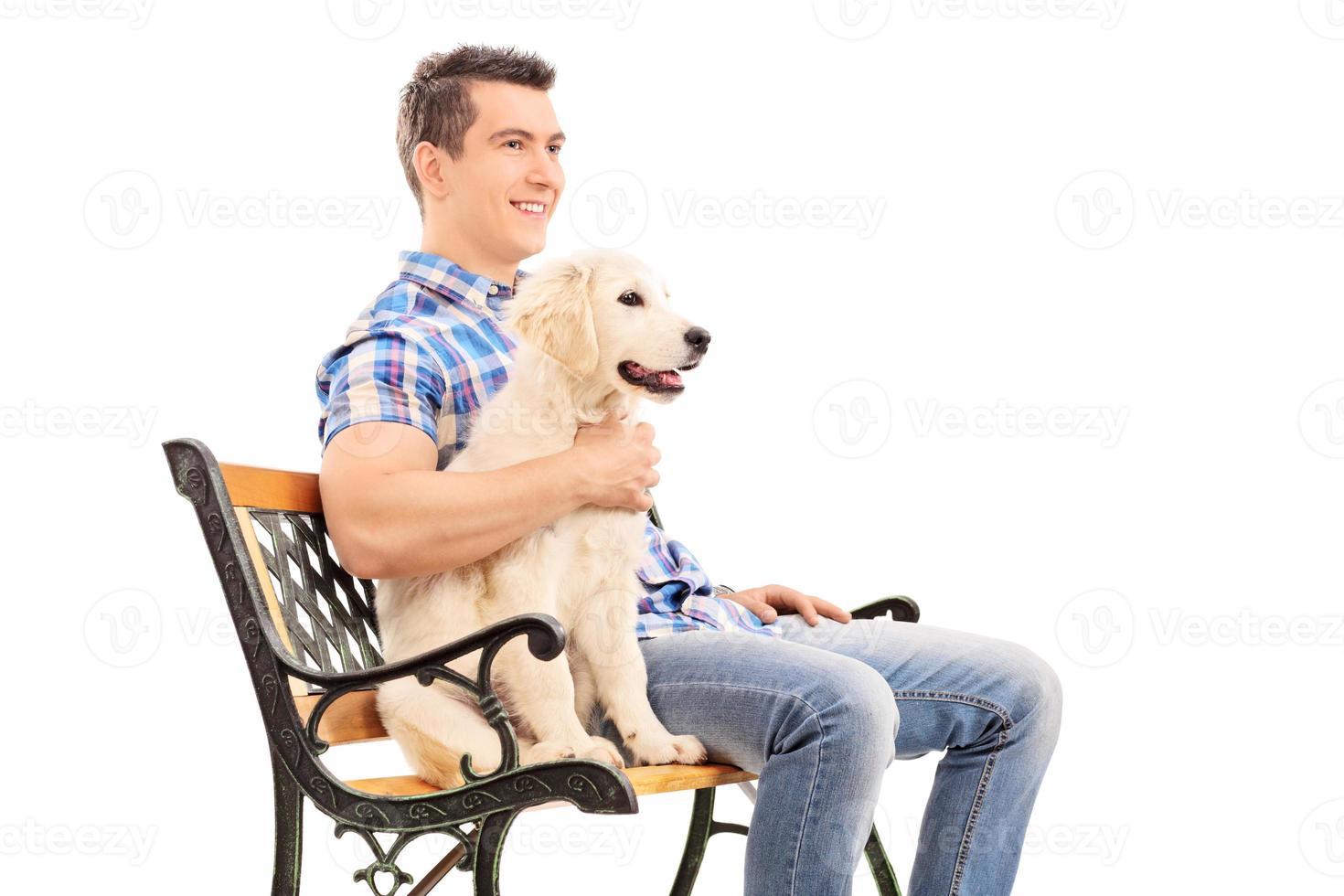 jovem sentado no banco com um filhote de cachorro foto