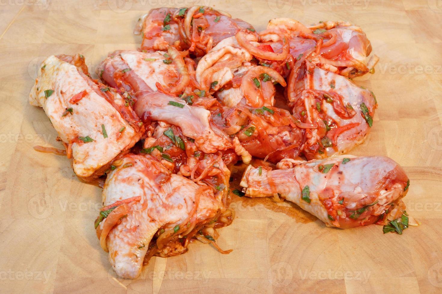 pedaços de frango marinado no fundo da tábua de madeira foto