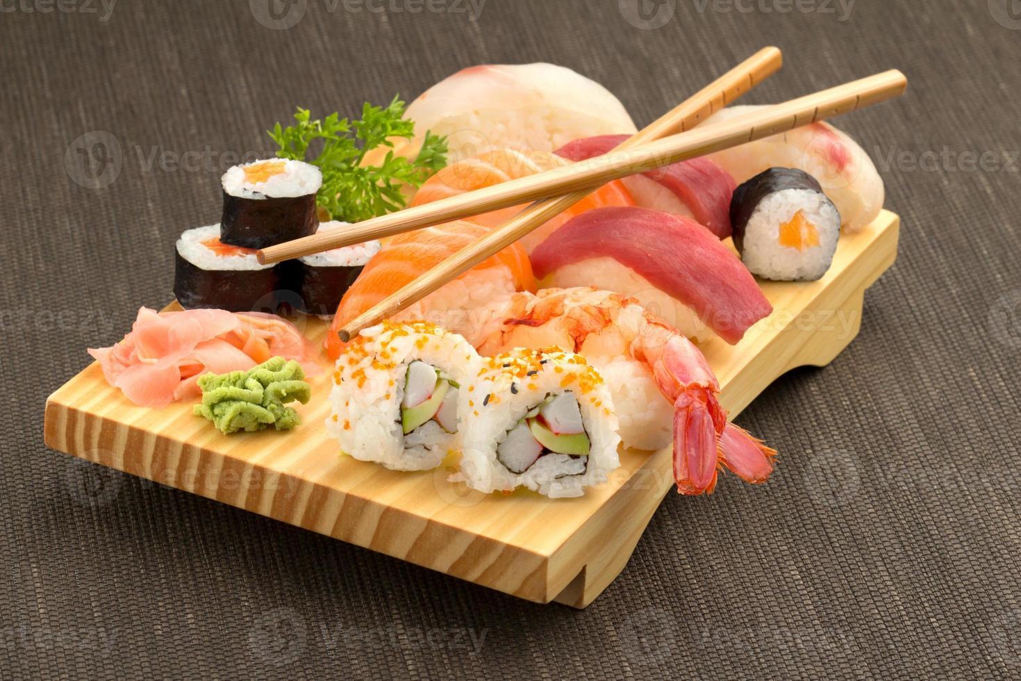 sushi e pauzinhos na placa de madeira foto