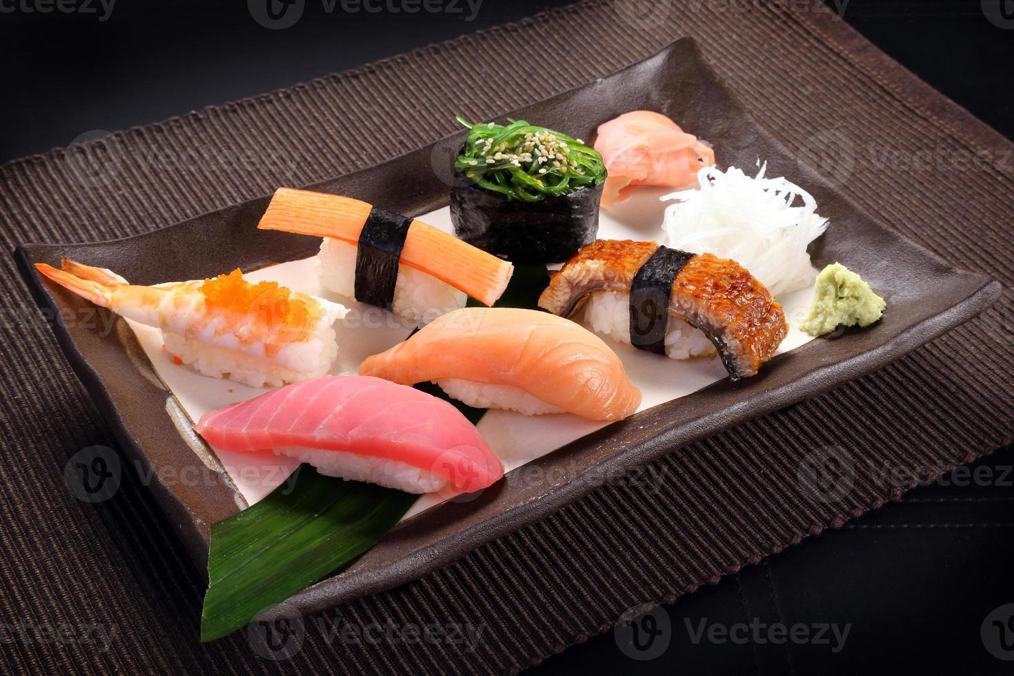 conjunto de sushi misto com wasabi no prato de cerâmica foto