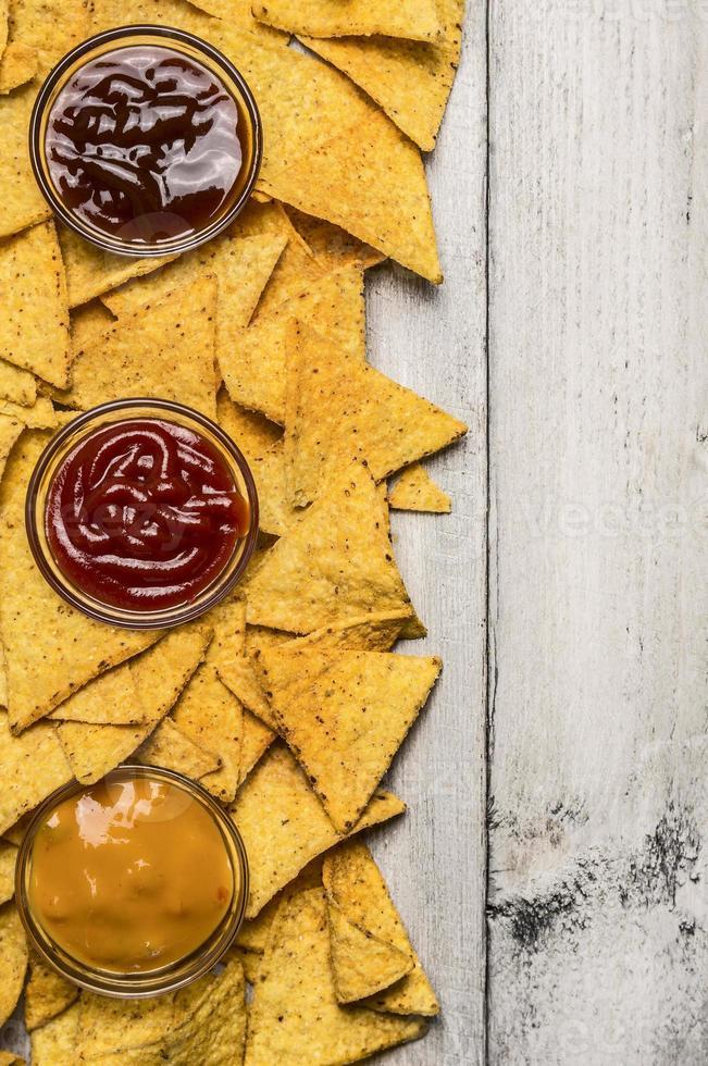 nacho chips mexicanos e mergulho colorido na borda de taças de vidro foto
