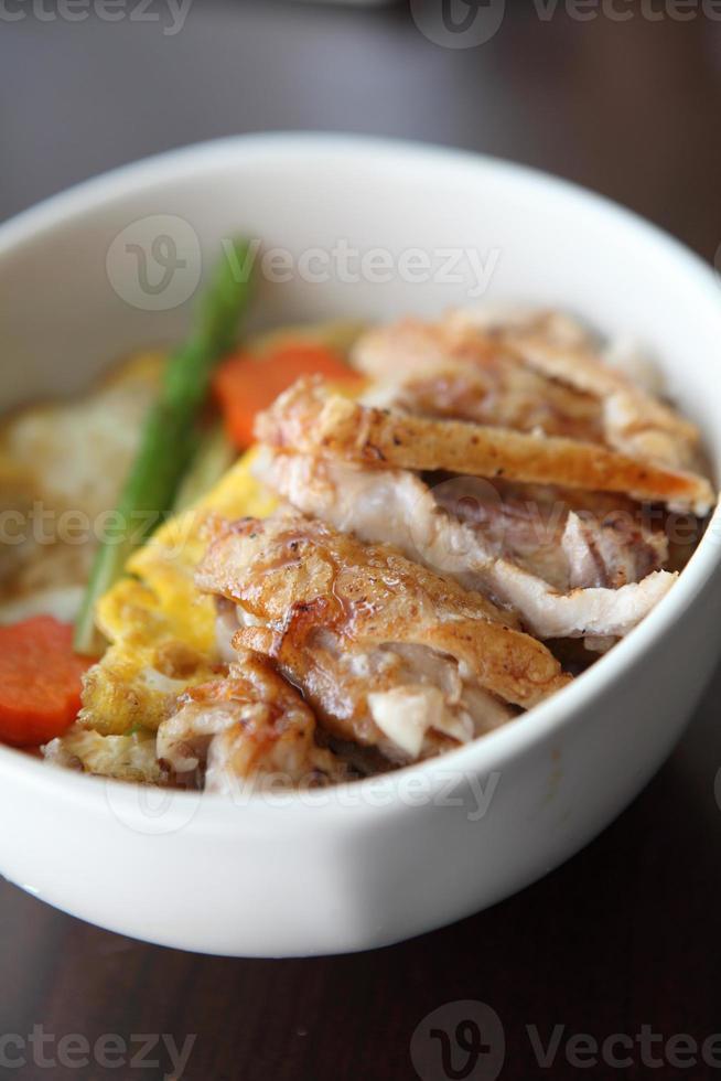arroz de frango grelhado teriyaki em fundo madeira foto