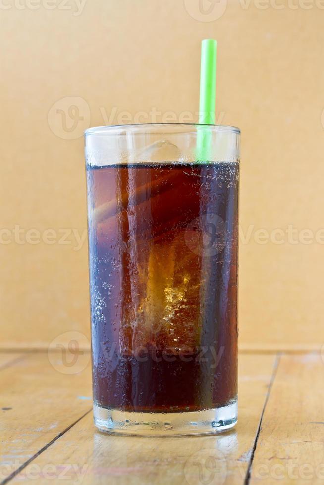 cola com gelo e palha no copo com fundo de madeira foto