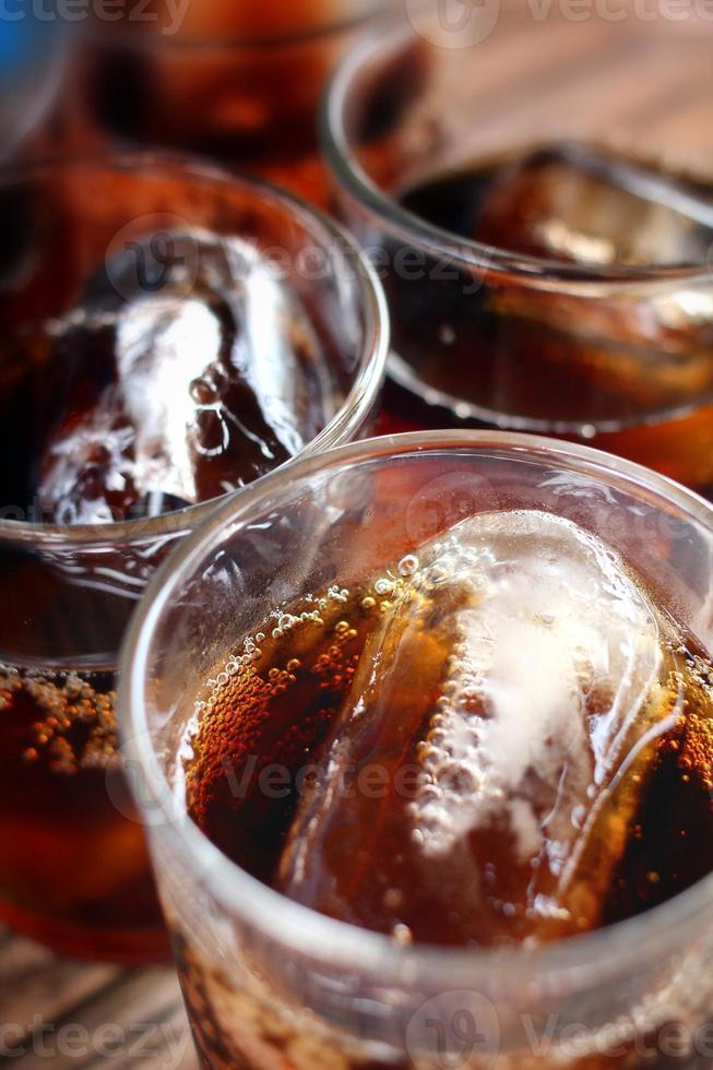 derramando um copo de coca-cola com gelo foto